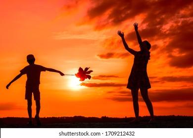 Silhouetten, die Jungen mit Windmühle spielen, und Mädchen mit Ball in der Natur auf bewölktem Himmelshintergrund