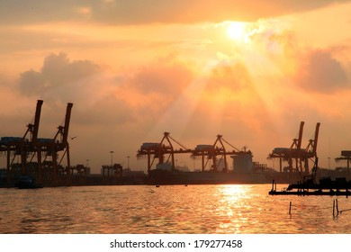 Silhouettes of port constructions crane on dark sunset with reflection water