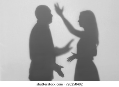 Silhouettes of quarreling man and woman on white background. Domestic violence concept
