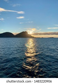 Silhouettes of rocky islands against the (almost) midnight sun.   Photo taken circa 1100-1115pm. View from the ferry travelling between Vaeroy and Moskenes. Lofoten, Nordland / Norway - June 20 2019