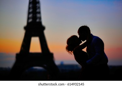 Silhouettes of a romantic couple kissing in front of the Eiffel tower at sunrise in Paris, France