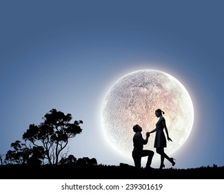 Silhouettes of romantic couple under the moon light