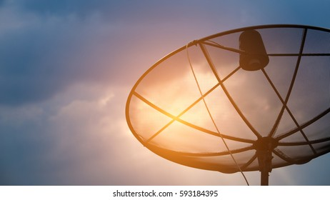 Silhouettes of Satellite dish on roof with sunset.