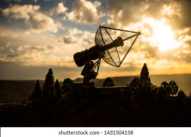 Silhouettes of satellite dishes or radio antennas against night sky. Space observatory or Air defence radar over dramatic sunset sky. Creative artwork decoration. Selective focus