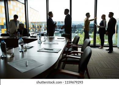 Silhouettes of several delegates standing in conference hall and discussing working points and reports