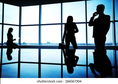 Silhouettes of several office workers working in office