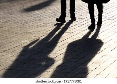 Silhouettes and shadows of couple walking down the street. Male and female legs, concept of relationships, city life, dramatic stories