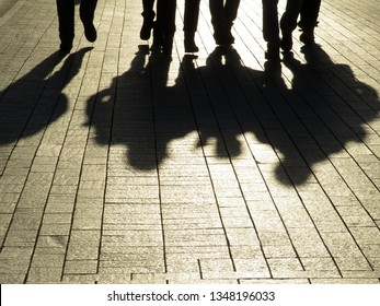 Silhouettes and shadows of people on the street. Crowd walking down on sidewalk, concept of strangers, crime, mafia, society, street gang