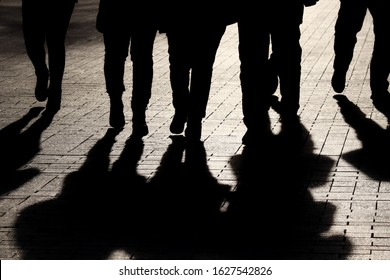 Silhouettes and shadows of people on the street. Crowd walking down on sidewalk, concept of strangers, crime, society, epidemic, population