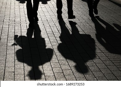 Silhouettes and shadows of people on the street. Concept of social distance, spread of infection during COVID-19 coronavirus pandemic, society and population