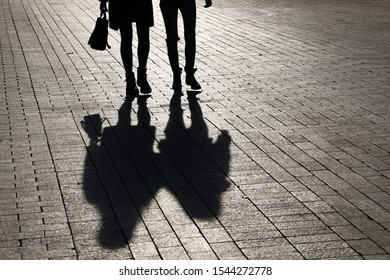 Silhouettes and shadows of two slim women walking down the street. Concept of female friendship, dramatic life