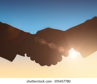 Silhouettes shaking hands against sun shining