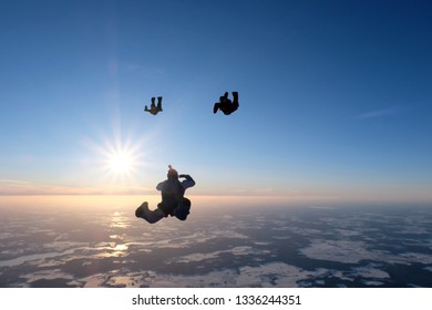 The silhouettes of skydivers above sunrise.