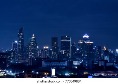 Silhouettes of skyscrapers in the dark town and blue background.