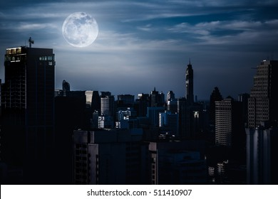 Silhouettes of skyscrapers different construction in the dark town with background of a large moon and clouds at nighttime. Dark tone and high contrast style. The moon were NOT furnished by NASA.