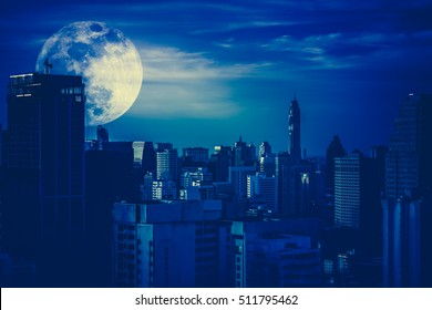 Silhouettes of skyscrapers different construction in the dark town with background of a large moon and clouds at nighttime. Dark tone. The moon were NOT furnished by NASA.
