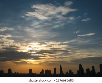 Silhouettes of the skyscrapers in downtown Bangkok cityscapes, the capital of Thailand in southeast Asia, with golden sunshine at sunset in summer in horizontal view.