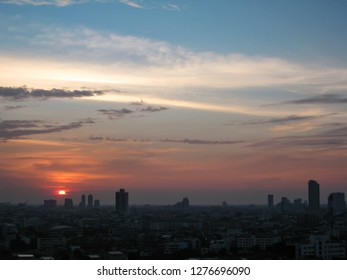 Silhouettes of the skyscrapers in downtown Bangkok cityscapes, the capital of Thailand in southeast Asia, with white cloud, blue sky and red sunshine evening at sunset in winter in horizontal view.