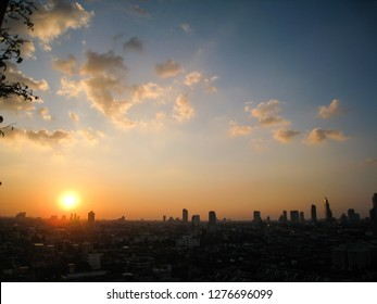 Silhouettes of the skyscrapers in downtown Bangkok cityscapes, the capital of Thailand in southeast Asia, with white cloud, blue sky and golden sunshine evening at sunset in winter in horizontal view.
