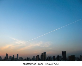 Silhouettes of the skyscrapers in downtown Bangkok cityscapes, the capital of Thailand in southeast Asia, with  condensation trails on clear blue sky at sunshine evening in summer in horizontal view.
