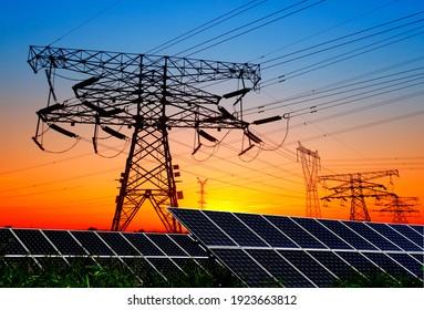 Silhouetten von Umspannstationen und Solarzellen. Sonnenkollektoren und Hochspannungstürme am Abend