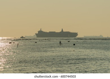 silhouettes of surfers and stand-up paddle boarders on the pacific ocean with large ships in the background sailing out of Honolulu Harbor