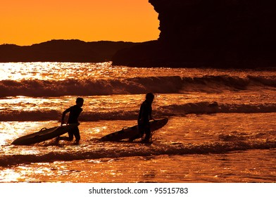 Silhouettes of surfers walking out of the sea