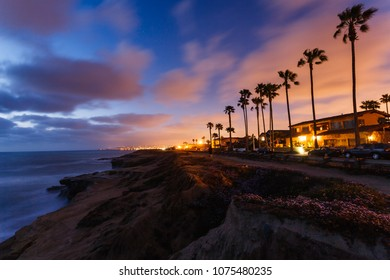 Silhouettes of tall palms and houses lit up at sunset on ocean cliffs