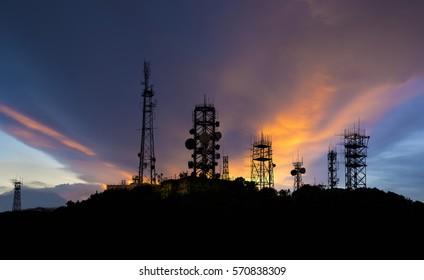 Silhouettes Telecommunication mast television antennas on sunlight background