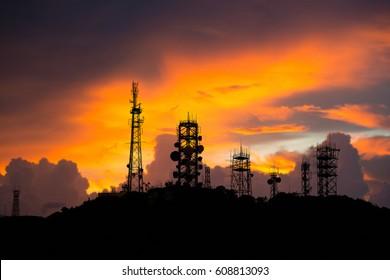 Silhouettes Telecommunication mast television antennas on sunlight background.