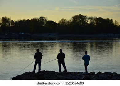 The silhouettes of three anglers by the river Rhine at sunset in autumn. Rhein-Neckar-Kreis, Baden-Wuerttemberg, Germany.