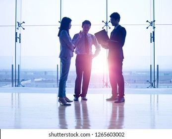 silhouettes of three asian corporate executives standing in front of windows discussing business using laptop computer.