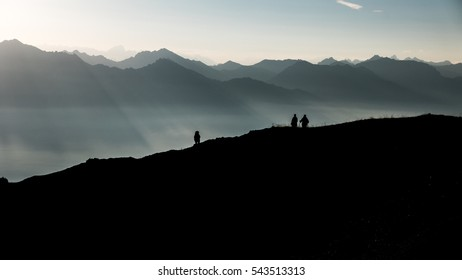 The silhouettes of three hikers against mountains in Switzerland