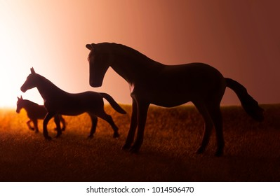 Silhouettes Of Three Horses Pasturing On Sunset Background