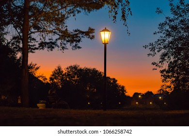 Silhouettes of three lampposts of street lighting form a perspective of a triangle against the sunset over the horizon, in the background silhouettes of sity, houses, trees, blue-orange-red background