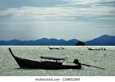 Silhouettes of three long tail boats in the Ao Nang bay, Krabi province, Thailand