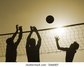 Silhouettes of three men playing beach volleyball,