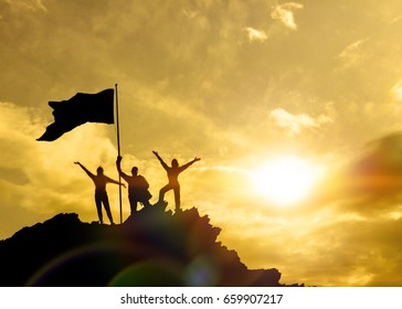 Silhouettes of three people holding a victory flag on top of a mountain, family. A man on top of a mountain. Concept idea, success in business. Against the sky at sunset.