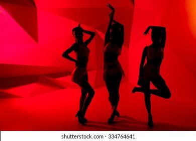 Silhouettes of three slim posturing girls