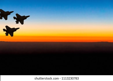 Silhouettes of three super modern fighter-bomber aircraft F-35 on sunset sky background
