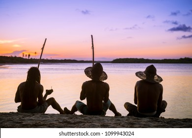 Silhouettes of three unrecognizable capoeiristas sat on the beach paying berimbau and drum instruments while watching the sunset in Bahia, Brazil.