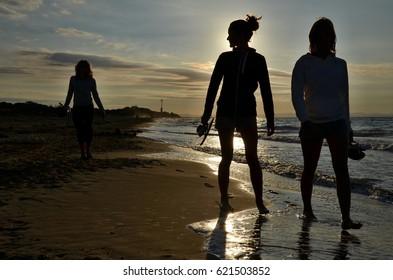 silhouettes of three women walking on the beach