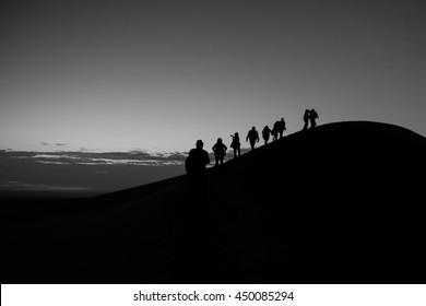 Silhouettes of tourist team on mountain peak