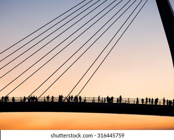 Silhouettes of tourists on the bridge in sunset