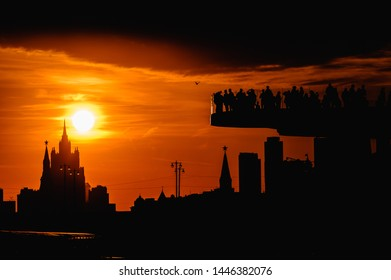 Silhouettes of Tourists on the Floating bridge in Zaryadye Park, Kremlin and The Kremlin Embankment while sunset on the background
