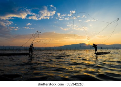 Silhouettes of the traditional fishermen throwing fishing net during sunrise, phayao, Thailand