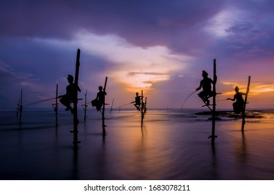 Silhouettes Of The Traditional Sri Lankan Stilt Fishermen At The Sunset In Koggala, Sri Lanka. Stilt Fishing Is A Method Of Fishing Unique To The Island (With The Computer Color Effect)