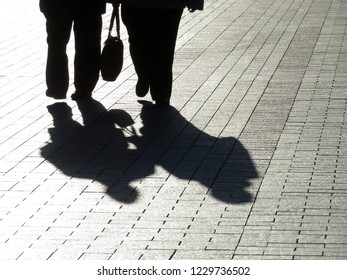 Silhouettes of two adult people walking down on the street. Elderly couple outdoors, shadows on pavement, fat people