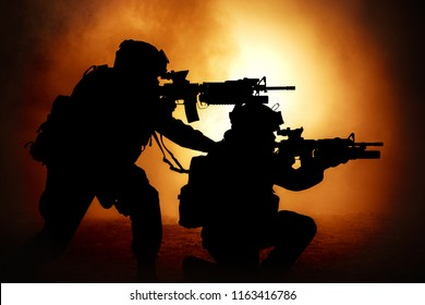 Silhouettes of two army soldiers, U.S. marines team in action, surrounded fire and smoke, shooting with assault rifle and machine gun, attacking enemy with suppressive gunfire during offensive mission