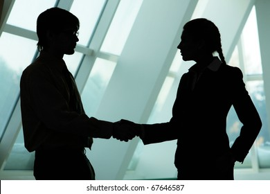 Silhouettes of two business partners handshaking and greeting each other